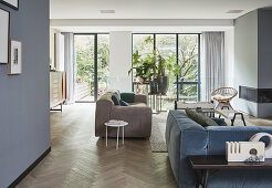 Blue and grey living room with glass wall leading to garden