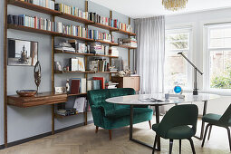 Sofa and upholstered chairs around oval dining room in front of wall-mounted shelving