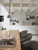View across long wooden table and upholstered chairs into open-plan kitchen