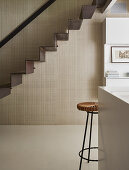 Self-supporting staircase made from a single piece of metal against beige wall