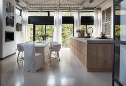 Grosse Kochinsel und langer, weisser Esstisch mit Hussenstühlen im Loft
