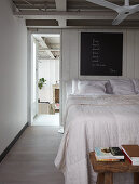 Double bed against white-painted board wall in loft apartment