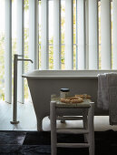 Free-standing bathtub in loft-apartment bathroom with vertical louvre blinds