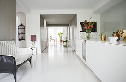 Sofa opposite white modern kitchen counter with long corridor in background