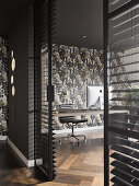View into office with patterned wallpaper and glass wall with louvre blinds