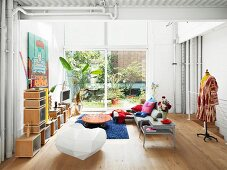 Regalmodulen, Designerstuhl und Kleiderpuppe in hohem Wohnzimmer mit Terrassentür