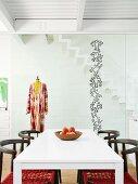 Weisser Esstisch mit Stühlen, im Hintergrund Kleiderpuppe vor Glastrennwand mit Fenster-Tattoo