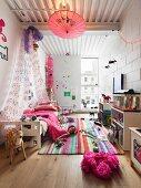 Kinderzimmer mit buntem Teppich, Baldachin-Bett und auf dem Boden spielendem Mädchen