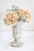 Dried hydrangeas and gypsophila in stone vase