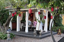 Garden party in pavilion surrounded by red lanterns