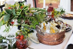 Various drinks in vintage tub, crayfish and flower arrangement on set table