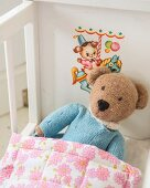 Knitted teddy bear in white retro dolls' bed