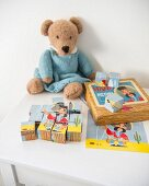 Building-block jigsaw and knitted teddy bear wearing dolls' dress on white child's table