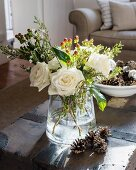 Wintry arrangement of white roses and pine cones