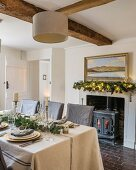 Festively set table in cottage with wooden beams and stone floor