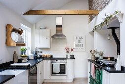Black and white country-house kitchen with sloping ceiling and wooden beam