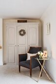 Side table and armchair in front of wardrobe with panelled doors