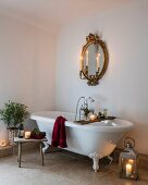 Romantic arrangement of candles around free-standing bathtub