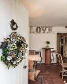 View past wreath on white front door into vintage cafe