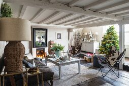 Fireplace, candlelight and Christmas tree in festive rustic living area
