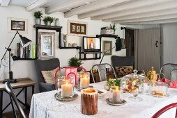 Black shelves made from piping and wooden boards and festively set dining table in cottage
