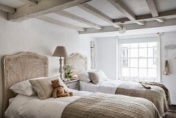 Twin beds with rattan headboards in bright, vintage bedroom with wood-beamed ceiling