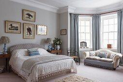 Elegant bedroom with sofa in window bay
