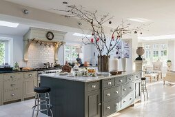 Bright, open-plan, country-house kitchen with arrangement of branches on island counter