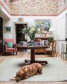 Dog lying on floor in front of table in classic interior