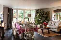 Table set for Christmas dinner and decorated Christmas tree in traditional country-house living room