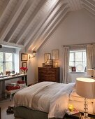 Chest of drawers and wrapped Christmas presents in country-house bedroom