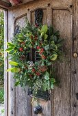 Festive wreath on rustic wooden front door