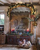 Large gilt-framed mirror above festive arrangement on trunk
