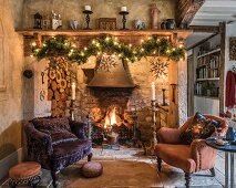 Two armchairs in front of open fireplace decorated with festive garland