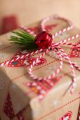 Red bell and fir sprig decorating wrapped present
