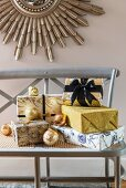 Presents glamorously wrapped in gold and blue on wooden bench