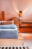 Simple bed on platform in wood-clad attic room