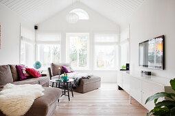 Helles Wohnzimmer mit offenem Dach und Fensterfront