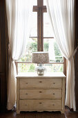 Table lamp with silver base on old chest of drawers below window
