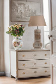 Vase of flowers and table lamp on white chest of drawers seen through open door