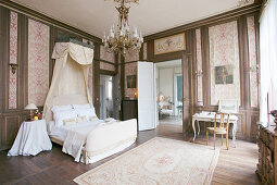 Bed with half-tester in historical bedroom with panelled walls