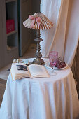 Open book and lamp on small table with white tablecloth