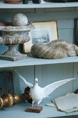 Stuffed dove and antique collectors items on shelves