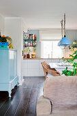 Blick auf weiße Küche und hellblau lackierte Kommode mit Türen in offenem Wohnraum