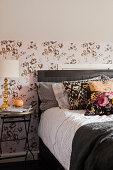 Doppelbett mit Kissen und Nachttisch mit Tischlampe vor tapezierter Wand
