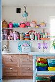Buntes Geschirr auf Wandregalen in der Küche mit Holzfronten
