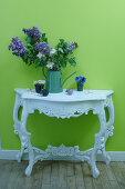 Vase on flowers on ornate console table against bright green wall