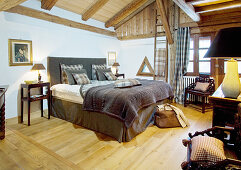 Brown and grey textiles on double bed in rustic bedroom with wood-beamed ceiling and lattice windows