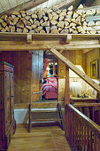 Landing with firewood stacked on beams in rustic chalet; view into bedroom