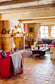 Red armchair, fireplace clad in wood, sofa set and coffee table in open-plan chalet interior
